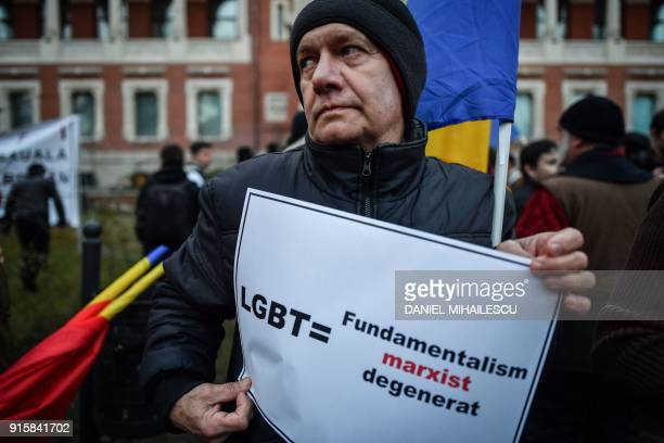 A man holds a leaflet reading 'LGBT= Marxism degenerated fundamentalism' during a protest in front of the Romanian Peasant's Museum in Bucharest...