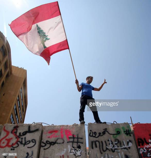 A man holds a Lebanese national flag as he stands on a concrete blast wall spread with graffiti depicting various political groups and bearing...