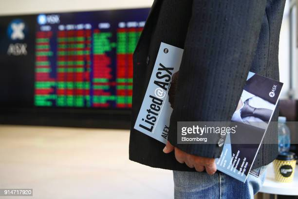 A man holds a Listed@ASX magazine while looking at an electronic board displaying stock information at the Australian Securities Exchange operated by...