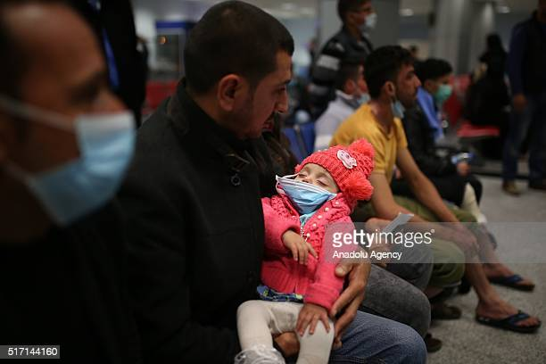 Man holds a little girl who has been affected by the mustard gas attack of ISIS in Tuz Khormatu District of Kirkuk at Erbil International Airport...
