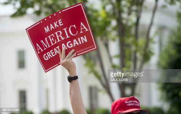 A man holds a Make America Great Again sign as supporters of US President Donald Trump and his policies demonstrate during a Pittsburgh Not Paris...