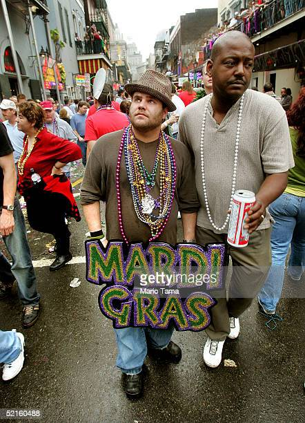 A man holds a Mardi Gras sign on Bourbon Street during Mardi Gras festivities February 8 2005 in New Orleans Louisiana Mardi Gras is the last...