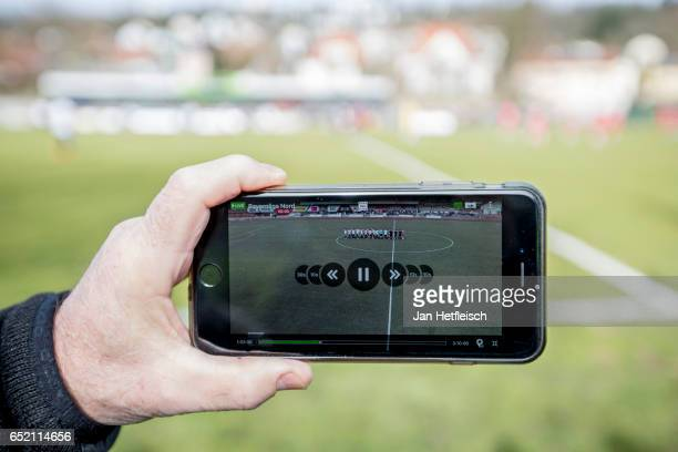 Man holds a mobile phone and watches the live broadcast of the soccer game VfB Eichstatt and TSV Aubstadt on March 11, 2017 in Eichstatt, Germany....