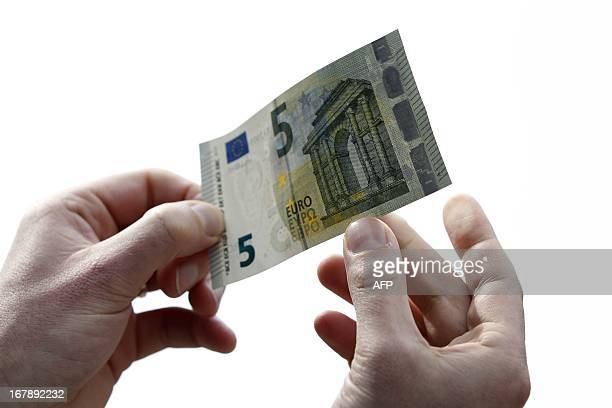 A man holds a new 5euro banknote in Amsterdam on May 2 2013 The first series of the lowest value euro banknote have been issued today The five euro...