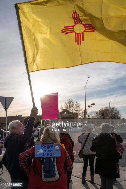A man holds a New Mexican flag during a Presidents Day protest against the US president's national emergency declaration in downtown Las Cruces New...