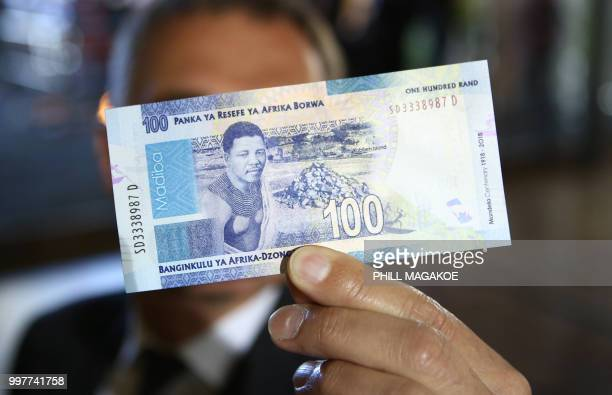 A man holds a new South African banknote at the value of one hundred South African Rand depicting former South African president Nelson Mandela at...
