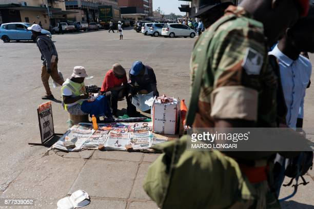 A man holds a newspaper stand on a street corner in Harare on November 22 the day after the resignation of President Robert Mugabe who ruled for 37...