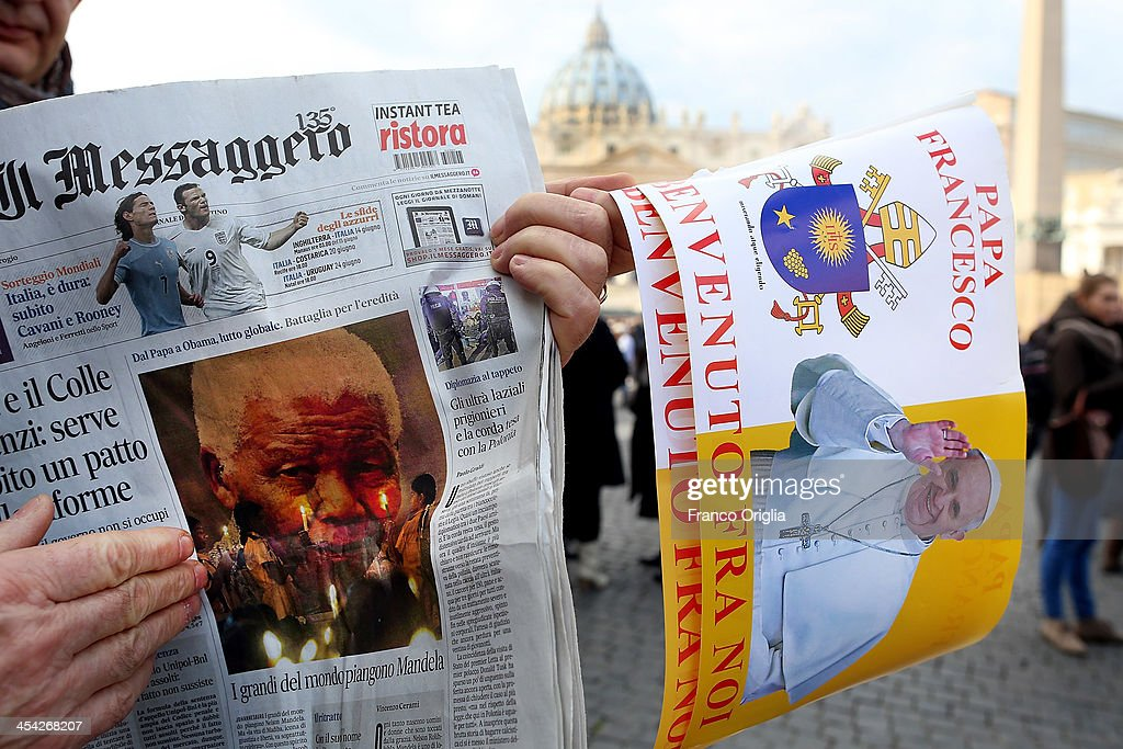 A man holds a newspaper with a photo of Nelson Mandela on the front page and a flag featuring Pope Francis in St Peter's Square during the Sunday Angelus blessing held by Pope Francis on December 8, 2013 in Vatican City, Vatican. Pope Francis on Friday paid tribute to Nelson Mandela expressing his hope that the late President's example will inspire generations of South Africans to put justice and common good at the forefront of their political aspirations.