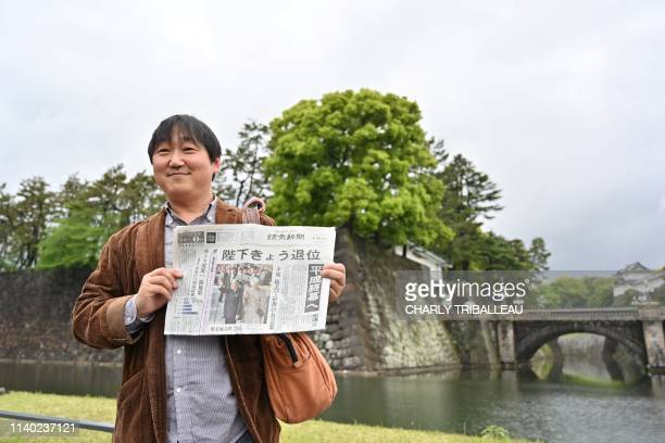 TOPSHOT A man holds a newspaper with an image of Japan's Emperor Akihito and Empress Michiko as poses at the grounds surrounding the Imperial Palace...