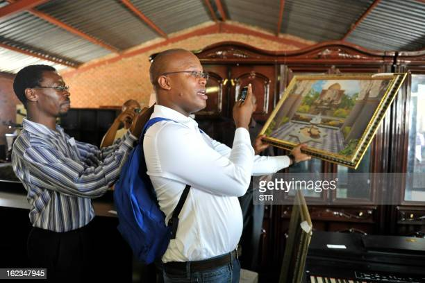 A man holds a painting formerly belonging to former ANC Youth League president Julius Malema during an auction of Malema's household goods at...