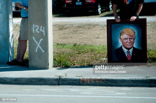 TOPSHOT A man holds a painting of US President Donald Trump as the president's motorcade passes while traveling to Palm Beach International Airport...