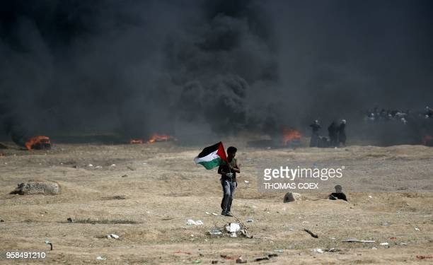 TOPSHOT A man holds a Palestinian flag during clashes with Israeli forces near the border between the Gaza strip and Israel east of Gaza City on May...