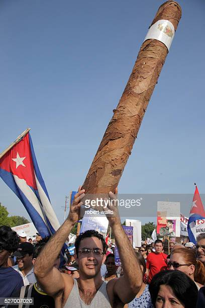 A man holds a papier mache cigar at First of May celebrations Tens of thousands flock to Plaza de la Revolucion for May Day speeches carrying flags...