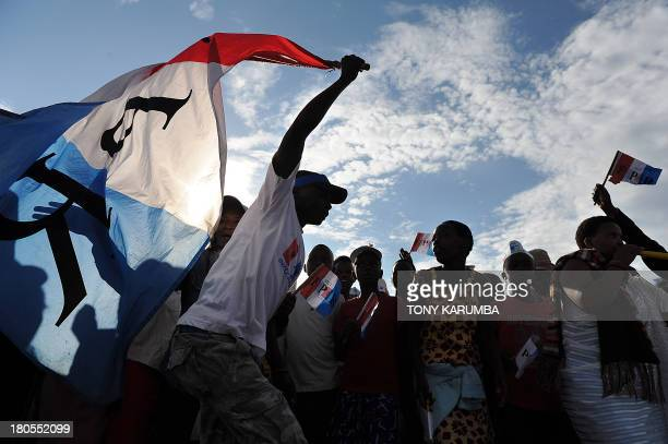 A man holds a party flag as supporters of the Rwandan President and the ruling Rwandan Patriotic Front party attend a campaign rally in the capital...