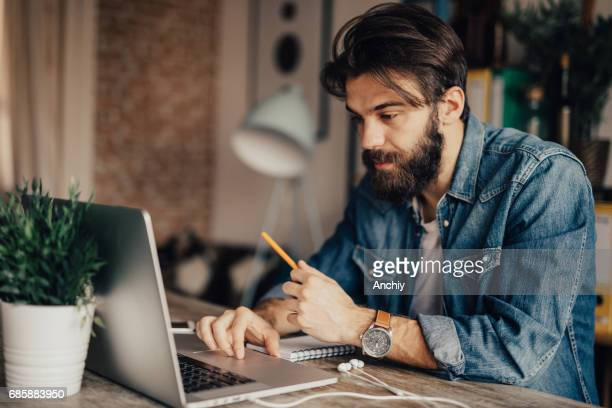A man holds a pen and uses laptop