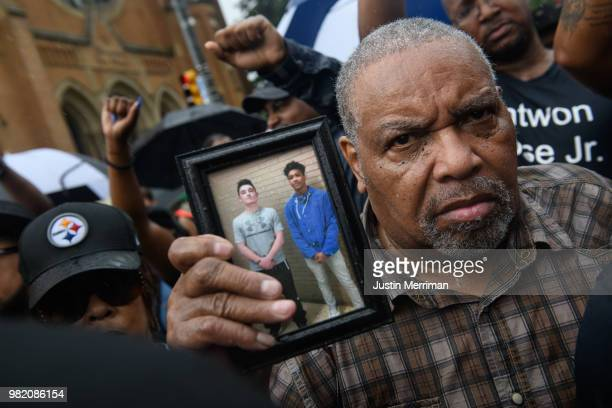 A man holds a photo of Antwon Rose as he joins a protest for the police shooting of Rose during a Juneteenth celebration on June 23 2018 in...