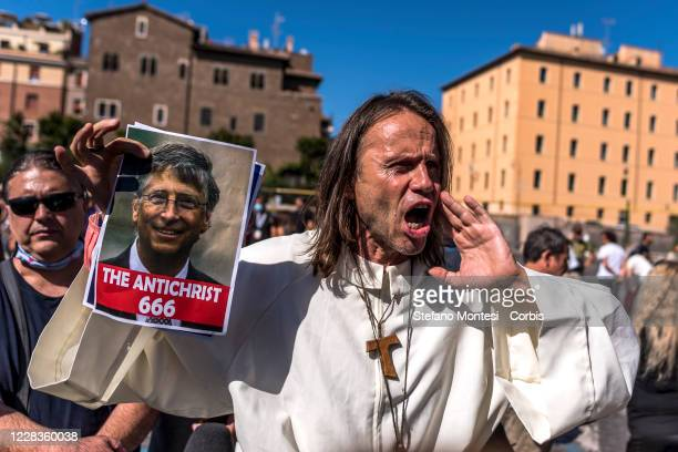 """Man holds a photo of Bill Gates and an inscription reading """" The Antichrist 666""""during the protest from """"No Mask"""" movements on September 5, 2020 in..."""