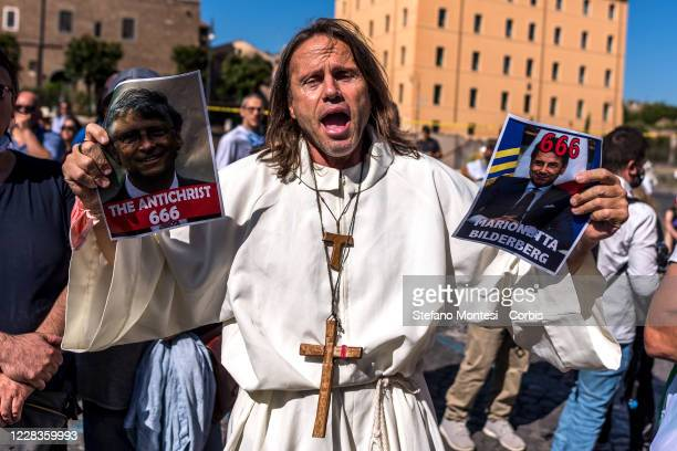 """Man holds a photo of Giuseppe Conte and an inscription reading """"Bilderberg Marionette"""" and a photo of Bill Gates and an inscription reading """" The..."""