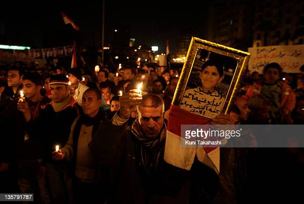 A man holds a photo of his relative at candle light vigil for the victims during uprising demanding President Hosni Mubarak to step down February 9...