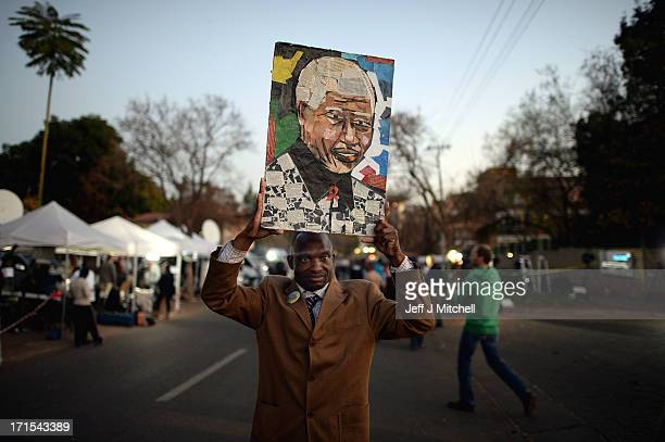 A man holds a picture as people gather to leave messages of support for former South African President Nelson Mandela outside the Mediclinic Heart...