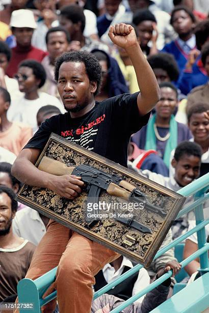 A man holds a picture of a Kalashnikov and raises his fist as jubilant inhabitants of Soweto attend a mass African National Congress rally to be...
