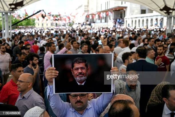 Man holds a picture of Egyptian President Mohamed Morsi during a symbolic funeral cerenomy on June 18, 2019 at Fatih mosque in Istanbul. - Thousands...