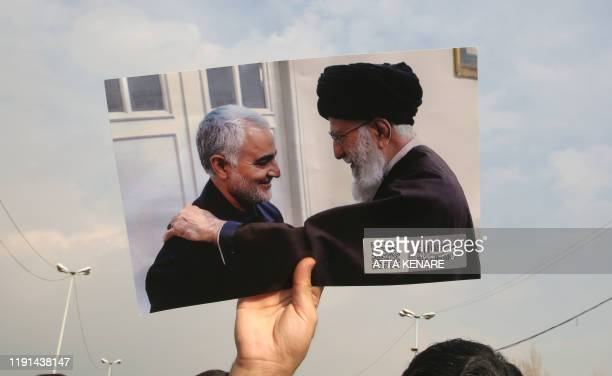 A man holds a picture of Iran's supreme leader Ayatollah Ali Khamenei with Iranian Revolutionary Guards top commander Qasem Soleimani during a...