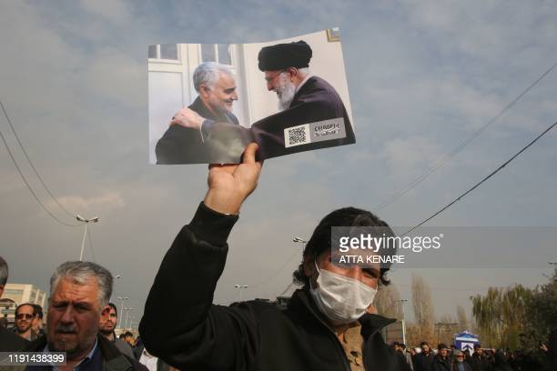 TOPSHOT A man holds a picture of Iran's supreme leader Ayatollah Ali Khamenei with Iranian Revolutionary Guards Major General Qasem Soleimani during...