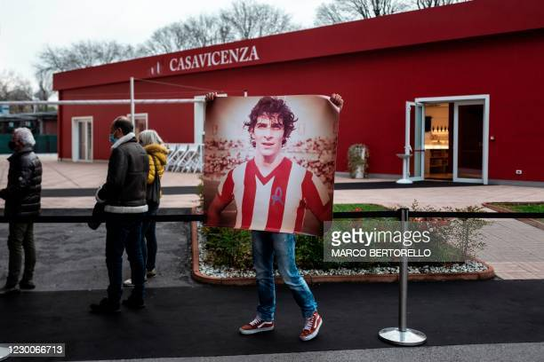 Man holds a picture of Italys football player Paolo Rossi as people queue to say a final farewell to the former Italian football player, while his...