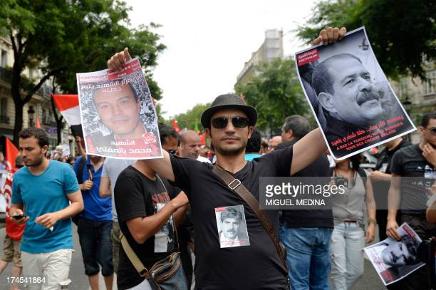 A man holds a picture of late Chokri Belaid during a demonstration to pay homage to the slain Tunisian opposition leader Mohamed Brahmi and to...