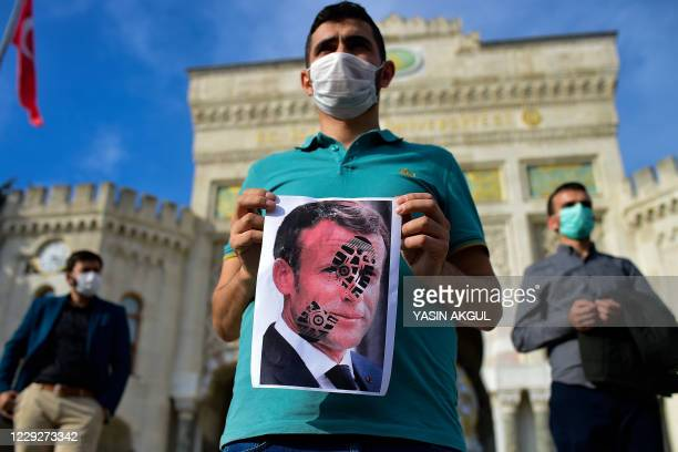 Man holds a picture of Macron with a shoe print on it as Turkish protesters shout slogans against France during a demonstration against French...