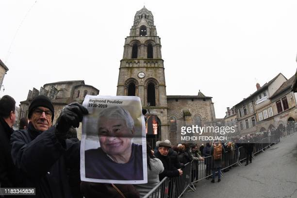 TOPSHOT A man holds a picture of Raymond Poulidor as people attend the funerals of the French cyclist in SaintLeonarddeNoblat on November 19 2019...