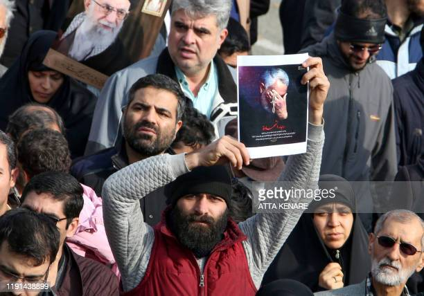 A man holds a picture of slain Iranian Revolutionary Guards Major General Qasem Soleimani during a demonstration in Tehran on January 3 2020 against...