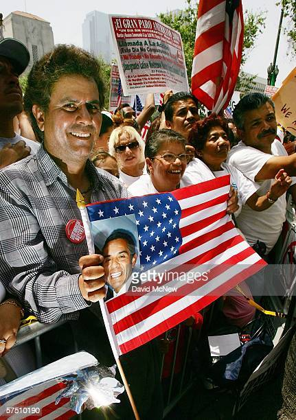 A man holds a picture of the Latino mayor of Los Angeles Antonio Villaraigosa at a rally on what is dubbed a Day Without Immigrants or the Great...