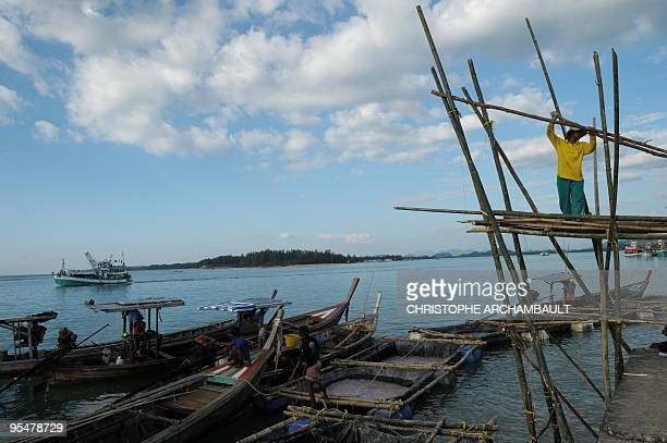 A man holds a piece of wood part of a structure used to lift heavy cargo from fishing boats at a pier at Ban Nam Khem one of Thailand's worstaffected...