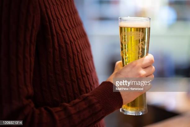 Man holds a pint of lager in a pub on February 28, 2020 in Cardiff, Wales. A new law setting a minimum alcohol price will come into force on March 2...