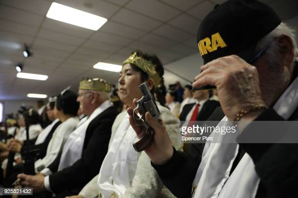 A man holds a pistol during a ceremony at the World Peace and Unification Sanctuary in Newfoundland Pennsylvania on February 28 2018 in Newfoundland...