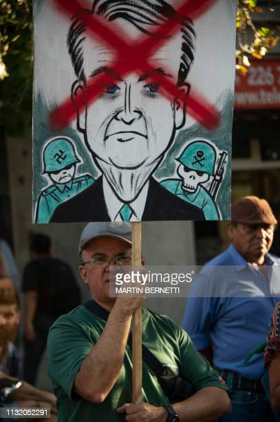 A man holds a placard as he demonstrates againts Brazilian President Jair Bolzonaro's visit during a protest called by Women and LGTB activists in...