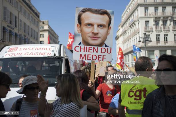 A man holds a placard bearing the portrait of French President and reading Dog of Medef [Medef is the French employers' association] as people...