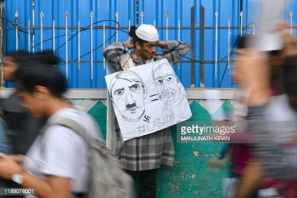 A man holds a placard comparing Indian Prime Minister Narendra Modi to German chancellor and Nazi Party leader Adolf Hitler at a protest against...