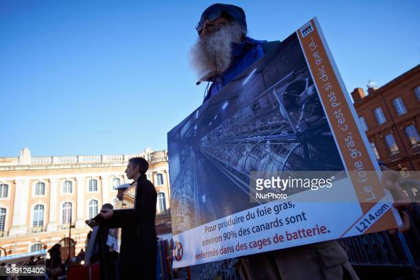 A man holds a placard depicting gooses in a farm and reading 'to produce foie gras nearly 90% of the ducks are in battery cages' The L214 association...