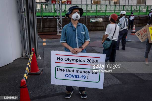 Man holds a placard during a demonstration against the forthcoming Tokyo Olympic Games on July 16, 2021 in Tokyo, Japan. Protesters gathered to...