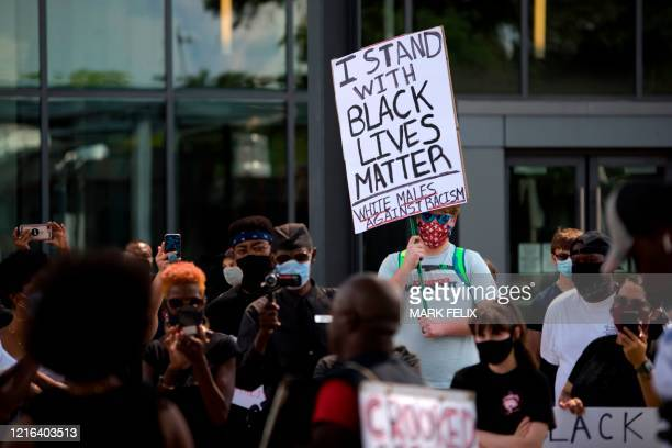 A man holds a placard during a Justice for George Floyd event in Houston Texas on May 30 after George Floyd an unarmed black died while being...
