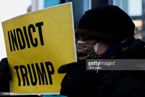 Man holds a placard during a protest against the former U.S. President Donald Trump at Trump Tower on March 08, 2021 in New York. Trump is returning...