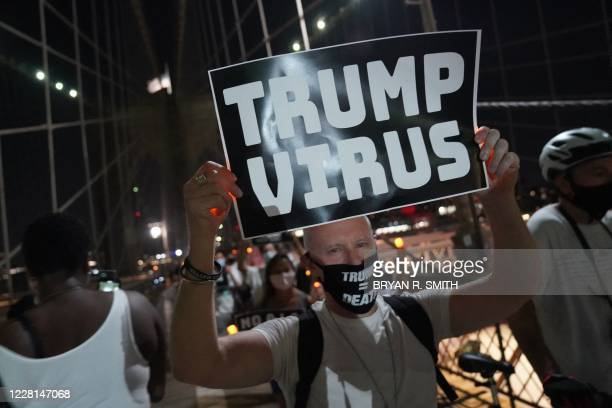 """Man holds a placard during the """"March for the Dead"""" across the Brooklyn Bridge, in memory of those who have died of COVID-19 and to protest the Trump..."""