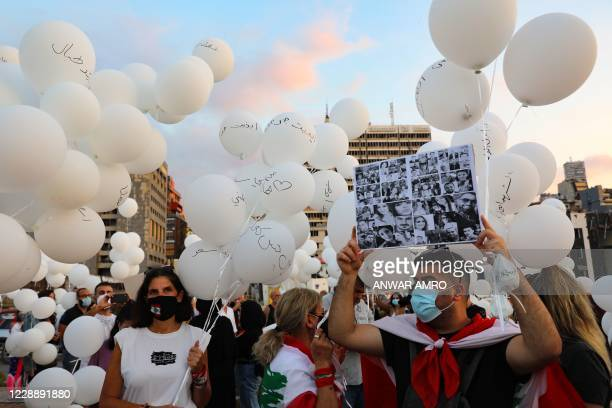 Man holds a placard near the seaport of Beirut on October 4 with pictures of people killed in the massive August 4 explosion there, as others prepare...