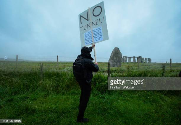 A man holds a placard protesting against the building of a tunnel at Stonehenge on June 21 2020 in Amesbury United Kingdom English Heritage which...