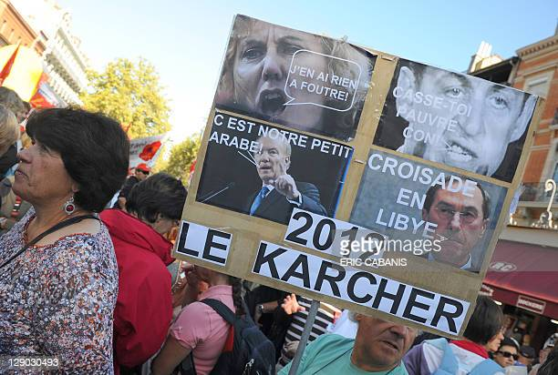 A man holds a placard reading ' 2012 the Karcher ' and showing pictures of entourage of France's president Nicolas Sarkozy during a in Toulouse...