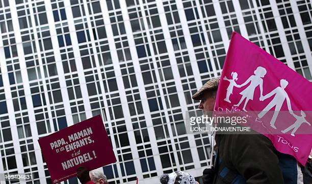 A man holds a placard reading 'A father a mother and children it's fundamental ' during a protest against samesex marriage in Paris on January 13...