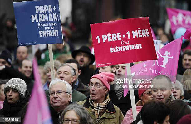 A man holds a placard reading 'A father and a mother it's fundamental ' during a march against samesex marriage on January 13 2013 in Paris Tens of...